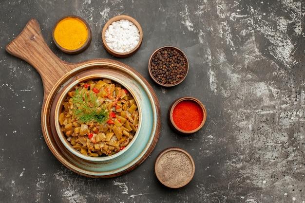 黒いテーブルの上の5種類のスパイスの横にトマトとトマトと豆の上部のクローズアップビュートマトとインゲンのボウル