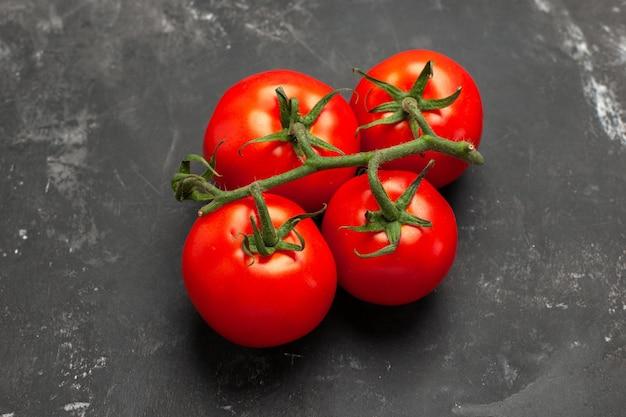 상단 클로즈업 보기 토마토 검정 테이블에 줄기가 있는 식욕을 돋우는 익은 토마토 4개