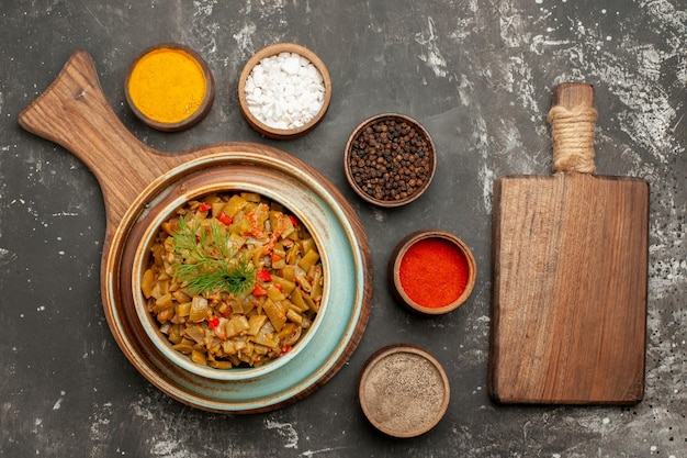 Vista ravvicinata dall'alto pomodori e fagiolini tagliere in legno ciotola di fagioli con pomodori accanto ai cinque tipi di spezie sul tavolo nero