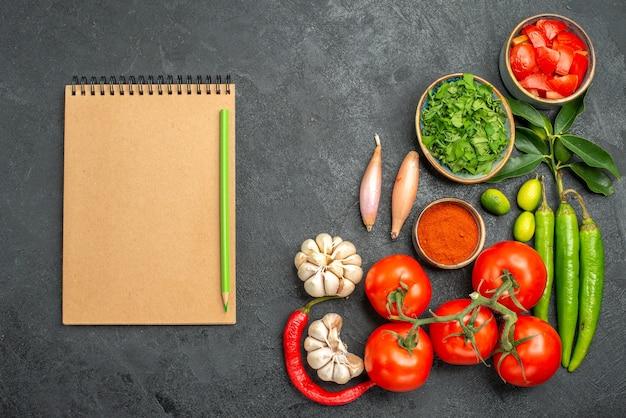 Вид сверху крупным планом томаты, блокнот, карандаш, рядом с мисками с разноцветными овощами, специями, травами