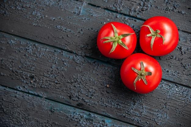 나무 회색 테이블에 빨간 익은 토마토 3개