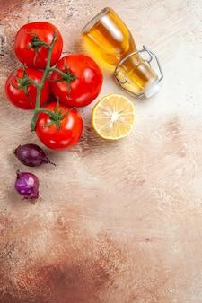 上のクローズアップビュートマトトマト玉ねぎレモンボトルのオイルテーブル