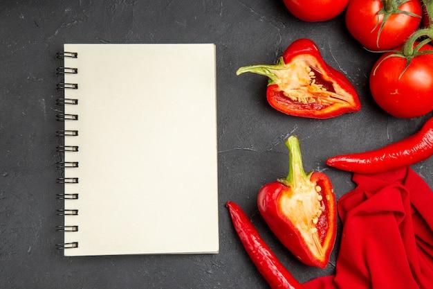 Вид сверху крупным планом овощи острый перец болгарский перец помидоры скатерть белая тетрадь