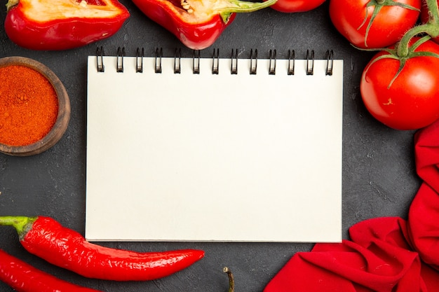 Вид сверху крупным планом овощи тетрадь скатерть специи болгарский перец помидоры острый перец