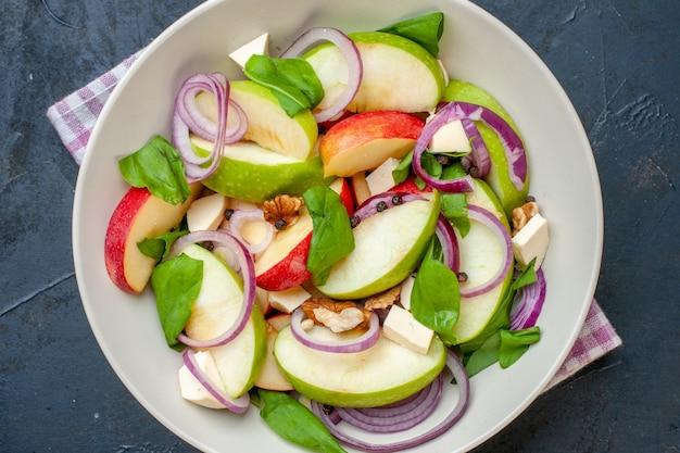 Сверху крупным планом яблочный салат в миске фиолетовая и белая клетчатая салфетка на темном столе