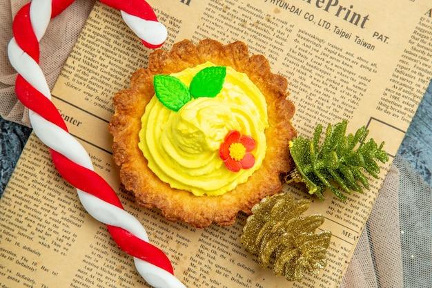 Biscotto con vista ravvicinata dall'alto con decorazioni natalizie di caramelle di natale crema su scialle beige di giornale su sfondo scuro