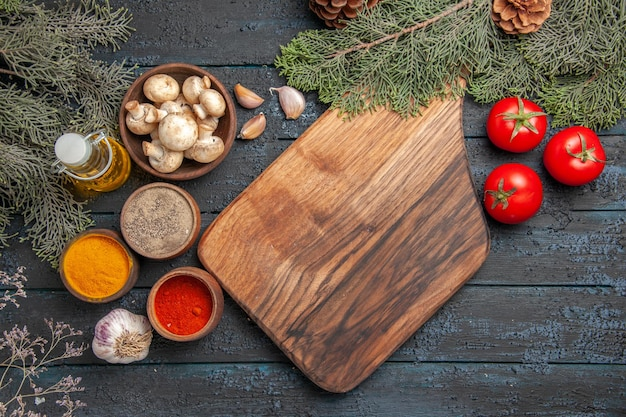 Top close view board and spices wooden brown cutting board next to fork garlic colorful spices oil in bottle three tomatoes and bowl of mushrooms under branches with cones