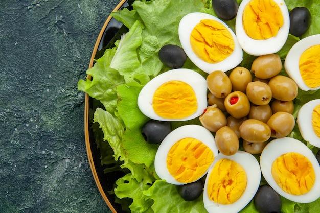 Сверху крупным планом вареные нарезанные яйца с оливками и зеленым салатом на темном фоне