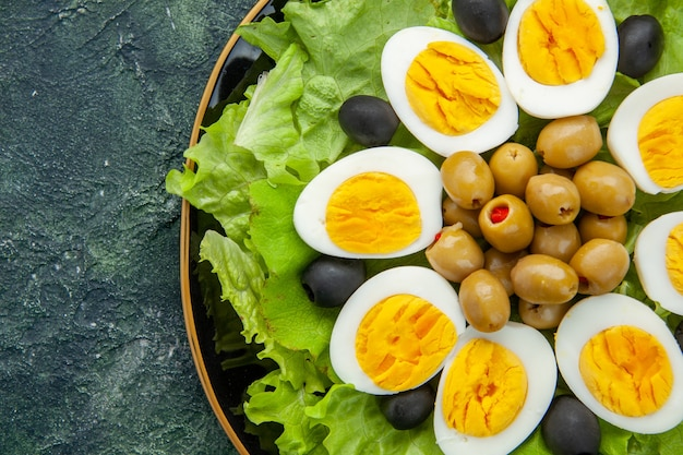 Vista dall'alto vicino uova bollite a fette con olive e insalata verde su sfondo scuro