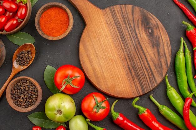 Vista ravvicinata dall'alto una ciotola di pomodorini peperoni rossi e verdi caldi e pomodori foglie di alloro ciotole di ketchup in polvere di peperoncino e pepe nero e un tagliere a terra