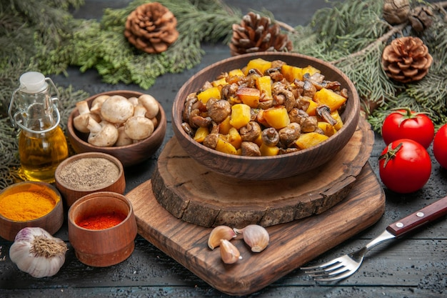Top close view bowl of food brown bowl of potatoes with mushrooms on cutting board next to fork garlic colorful spices oil in bottle and bowl of mushrooms under branches with cones