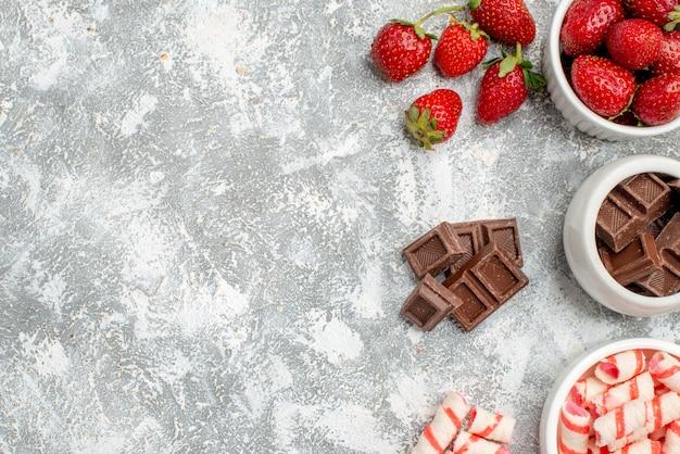 グレーホワイトの地面の右側にイチゴチョコレートキャンディーといくつかのイチゴチョコレートキャンディーが入った上部のクローズビューボウル