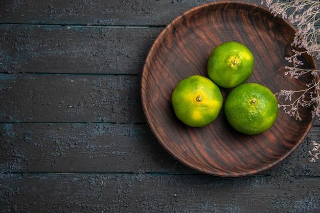 어두운 표면에 있는 가지 옆에 있는 갈색 그릇에 있는 상위 닫기 보기 가지와 라임 3개