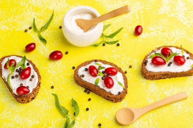 Vista ravvicinata dall'alto di toast di pane con panna acida e cornioli sulla superficie gialla