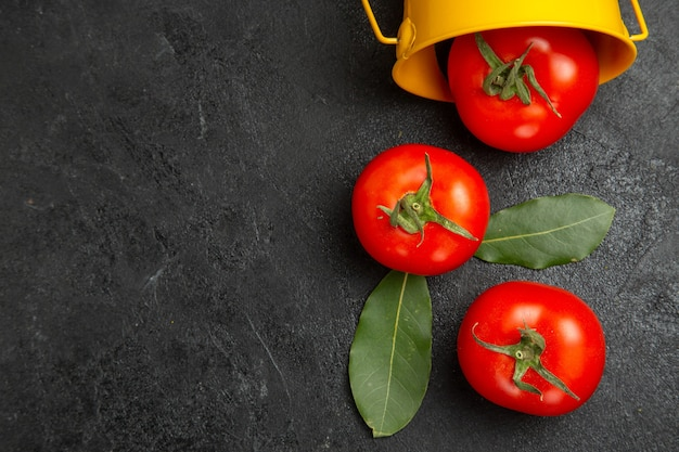 Top close view bucket with red tomatoes on dark table with copy space