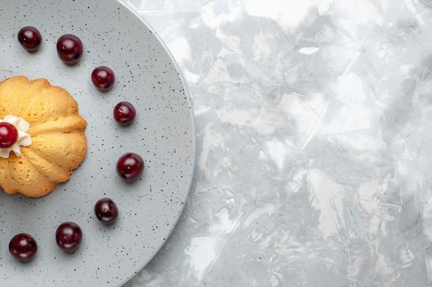 灰色のライトデスクにさくらんぼとトップクローズビューケーキ、ケーキビスケットクリームフルーツの写真