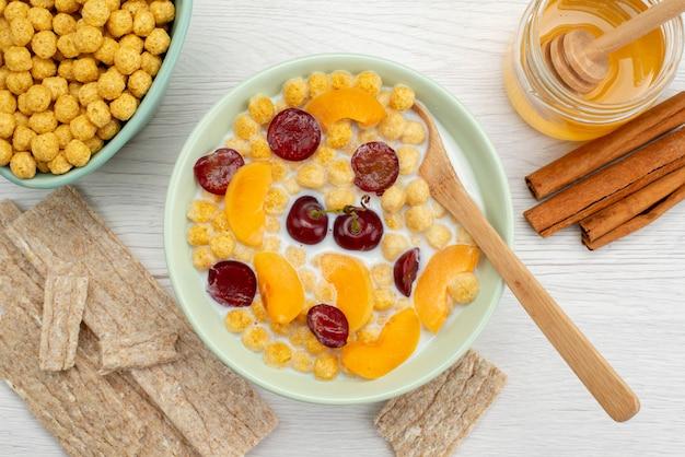 Cereali da vicino vista dall'alto con latte all'interno del piatto con cracker cannella e miele su bianco, bere latte colazione a base di latte da latte
