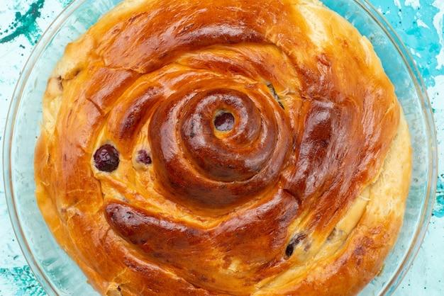 Torta di ciliegie vista dall'alto ravvicinata intera al forno con ciliegie all'interno su zucchero dolce azzurro e torta