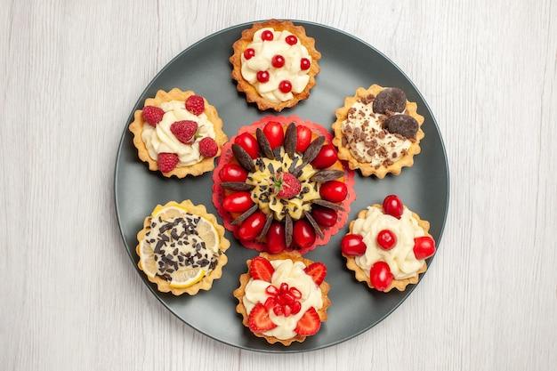 흰색 나무 테이블의 중앙에 회색 접시에 베리 타르트로 둥근 상단 가까이보기 초콜릿 케이크
