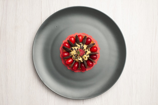 Top close view chocolate cake rounded with cornel and raspberry in the center in the grey plate on the white wooden background