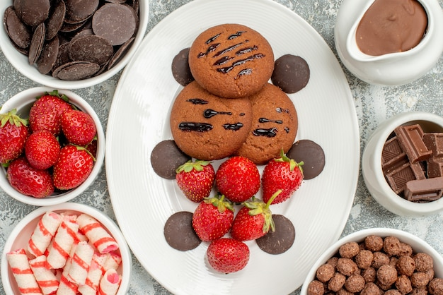 Top close view chocolate cookies strawberries and round chocolates on the white oval plate and bowls with candies strawberries chocolates cereals and cacao on the table