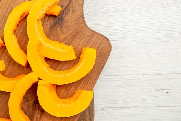 灰色のテーブルのまな板の上に刻んだバターナッツスカッシュを上から見る