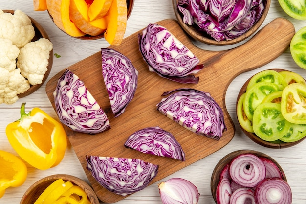 Top close view chopped red cabbage on wood board cut pupmkin cut green tomatoes cut yellow bell peppers in bowls on white surface