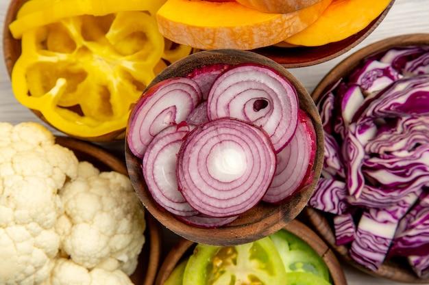 Top vista ravvicinata verdure tritate tagliate cavolo rosso tagliato zucca tagliata peperoni gialli tagliata cipolla tagliata pomodori verdi cavolfiore in ciotole sul tavolo bianco
