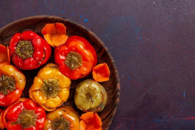 灰色の背景の食事野菜肉ドルマ食品の中にひき肉が入った調理済みピーマンを上から見る