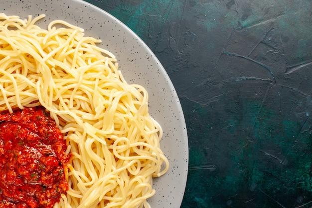 Вид сверху приготовленной итальянской пасты с фаршем и томатным соусом на темно-синей поверхности