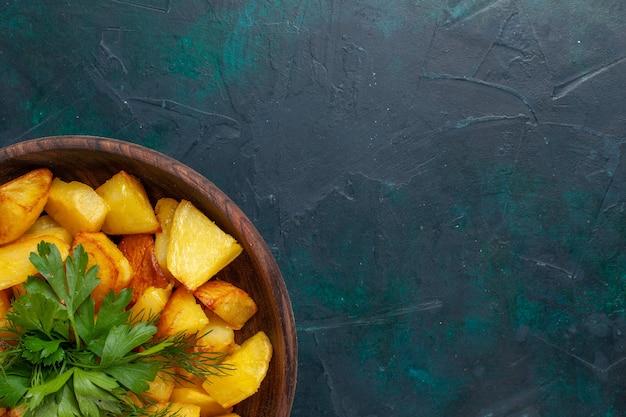 Vista ravvicinata dall'alto patate affettate cotte con verdure all'interno del piatto marrone su superficie blu scuro
