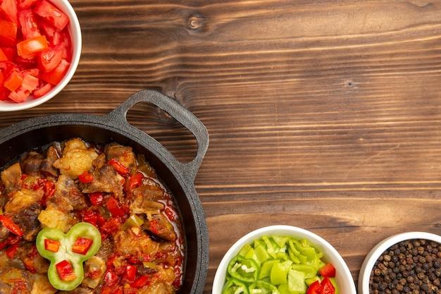 갈색 책상에 얇게 썬 피망 샐러드와 함께 상위 뷰 닫기 야채 식사 요리