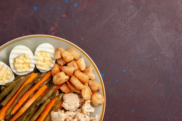 Vista ravvicinata dall'alto di verdure cotte con farina di uova su uno spazio buio