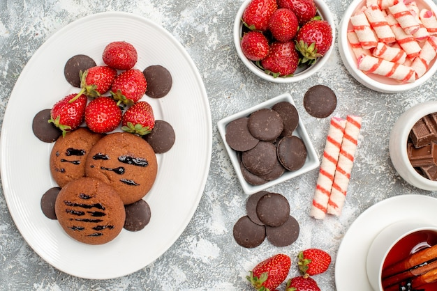 Top close view cookies strawberries and round chocolates on the oval plate bowls of candies strawberries chocolates and cinnamon tea on the grey-white table