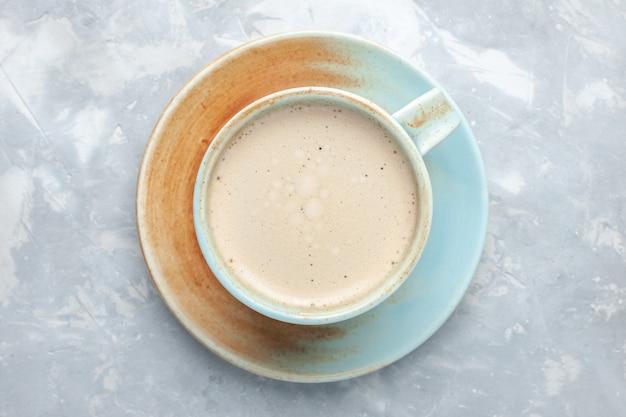 Top vista ravvicinata tazza di caffè con latte all'interno della tazza sulla scrivania bianca bere caffè latte scrivania colore