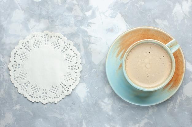 Top vista ravvicinata tazza di caffè con latte all'interno della tazza sullo scrittorio bianco bere caffè latte scrivania