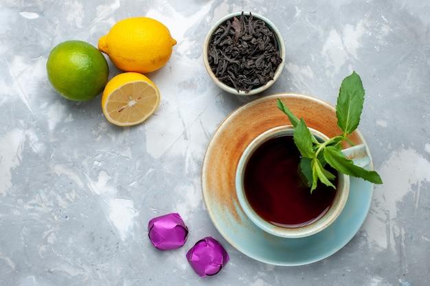 Вид сверху крупным планом чашка чая со свежими лимонами, конфетами и сушеным чаем на светлом столе, чай, фруктовый цвет цитрусовых