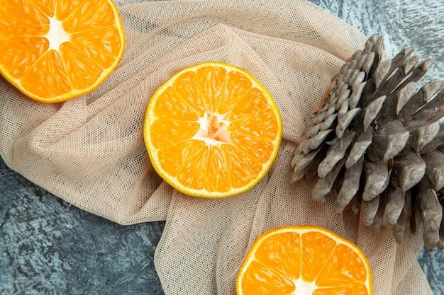Top close view cut oranges pinecones on beige shawl on dark surface