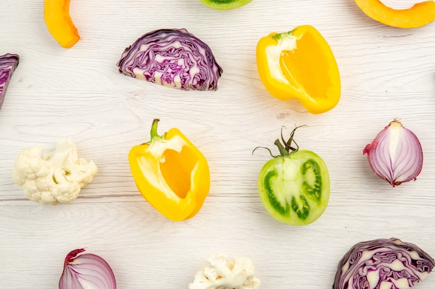 Top close view cut vegetables red cabbage green tomato pumpkin red onion yellow bell pepper caulifower on white surface