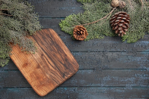 Top close view cutting board cutting board under spruce branches with cones