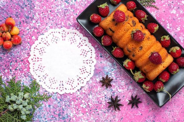 Сверху крупным планом вкусный испеченный торт внутри черной формы для торта со свежей красной клубникой на розовом столе.