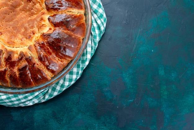 Сверху крупным планом вкусный испеченный торт круглой формы сладкий внутри стеклянной сковороды на светло-синем фоне.