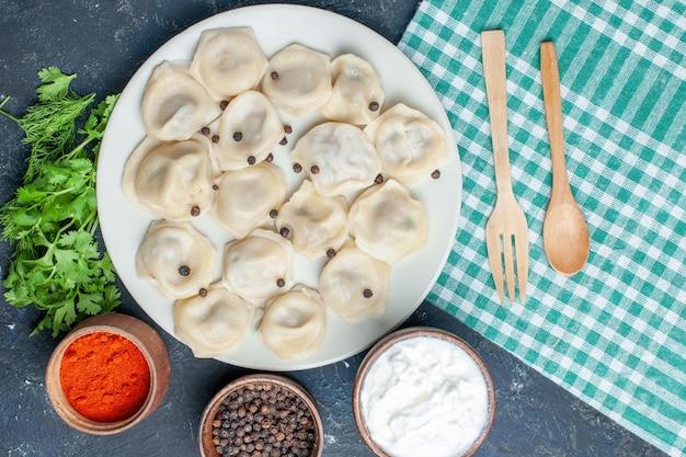 Vista ravvicinata dall'alto di deliziosi gnocchi al forno all'interno del piatto insieme a yogurt al pepe e verdure sulla scrivania scura, carne della cena del pasto della pasta