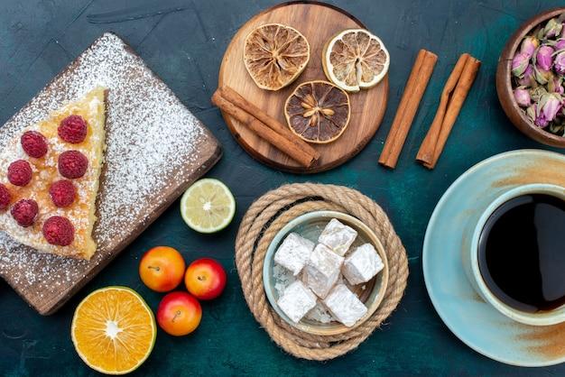 Top vista ravvicinata deliziosa fetta di torta con tè alla cannella e frutta sullo zucchero blu scuro della torta della torta della scrivania