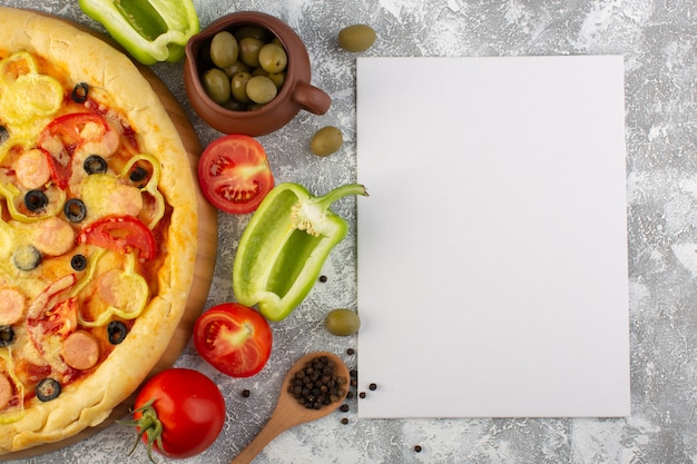 Вид сверху вкусной сырной пиццы с оливками, сосисками и помидорами на сером столе с бумажной пустой едой из итальянского теста быстрого питания