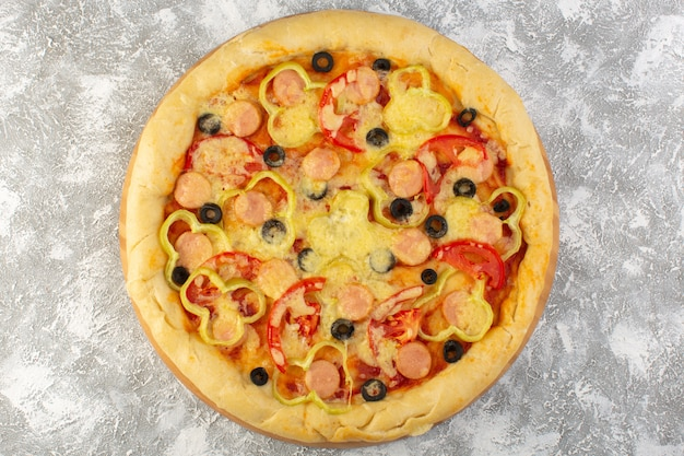 Top close view delicious cheesy pizza with olives sausages and tomatoes on the grey background fast-food italian dough food meal