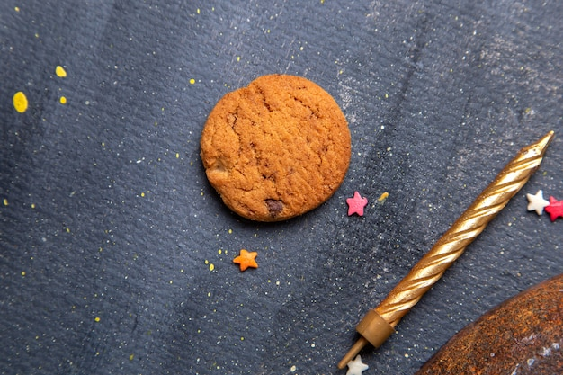 Top close view delicious chocolate cookie with golden candle on the dark background cookie biscuit sugar tea sweet