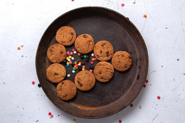 Сверху крупным планом вкусное шоколадное печенье внутри темной круглой тарелки на белом столе, печенье, печенье, сладкий чай