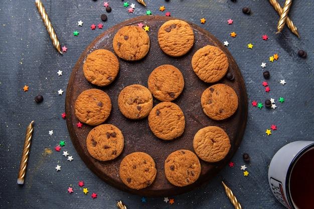 Вид сверху крупным планом вкусное шоколадное печенье со свечами и чаем на темном фоне печенье бисквит чай сладкий