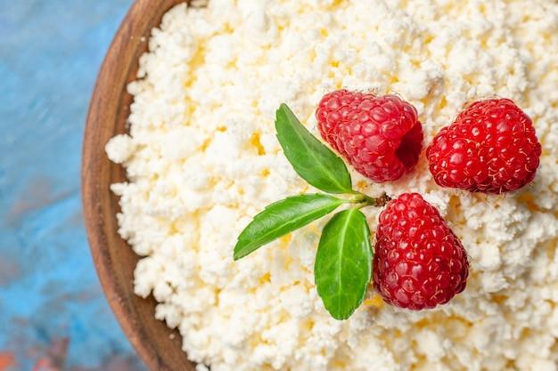 上部のクローズビュー青い背景の健康白い色のベリーの写真ミルクフルーツに新鮮なラズベリーとおいしいカッテージチーズ
